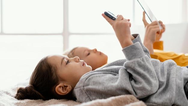 Fratelli germani a letto che giocano su cellulare e tablet