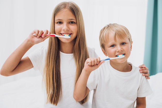 Siblings brushing their teeth together
