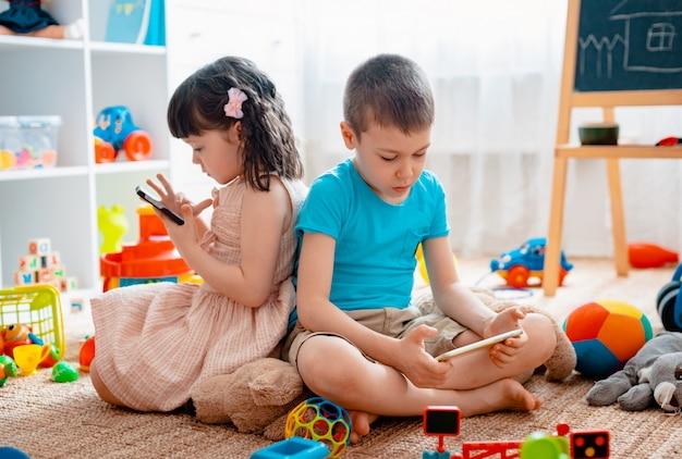 兄弟の子供たちの兄弟姉妹、友人は、散らばったおもちゃから切り離されたスマートフォンを備えた床の家の子供用プレイルームに座っています。