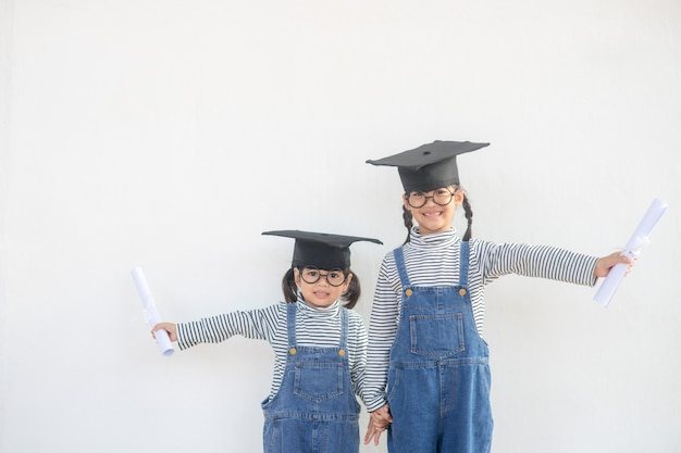 Siblings children girl graduation with cap and diploma over white.