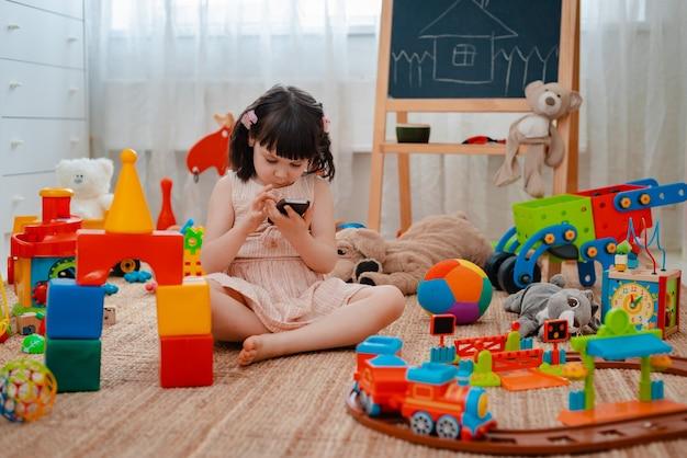 兄弟姉妹、友達が散らばったおもちゃから離れて、スマートフォンを持って子供用プレイルームの家の床に座っています。子供のための新しいガジェットの概念。