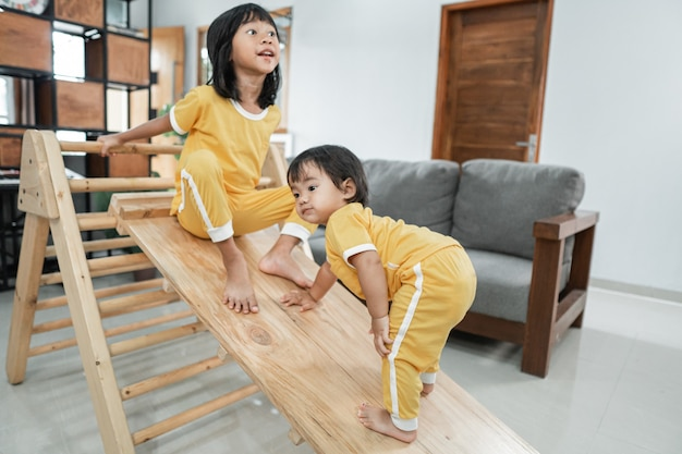 Siblings climb a pikler triangle toy together in the living room