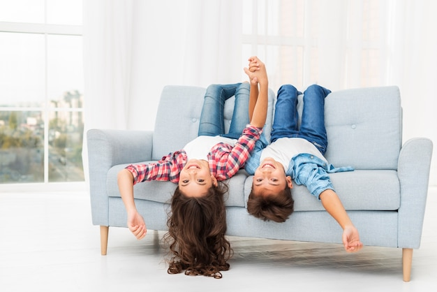 Siblings on couch edge with head hanging