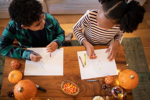 추수 감사절 저녁 식사 전에 함께 그림을 그리는 형제 자매