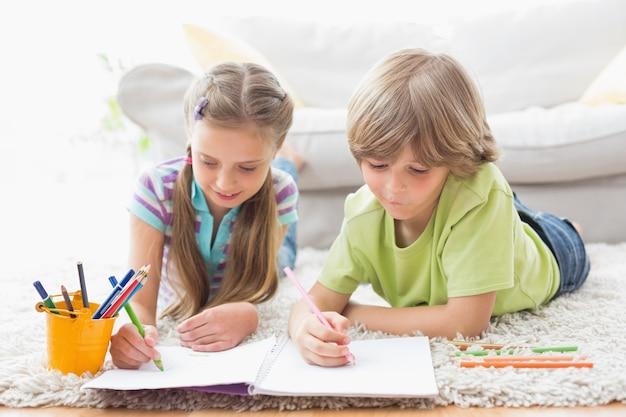 Братья и сестры, рисующие цветными карандашами, лежа на ковре
