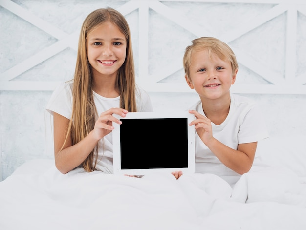 Siblings holding a tablet mock-up