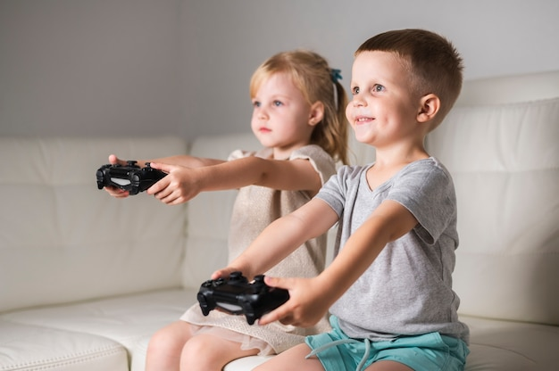 Siblings at home playing with joystick games