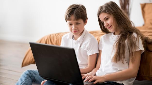 Siblings at home using laptop