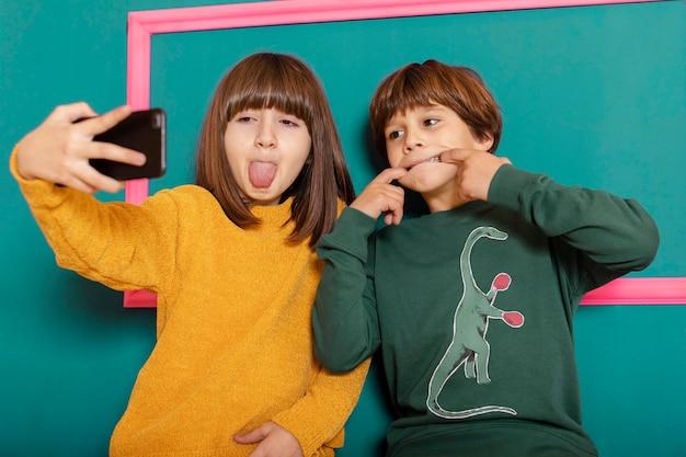 Siblings at home using mobile