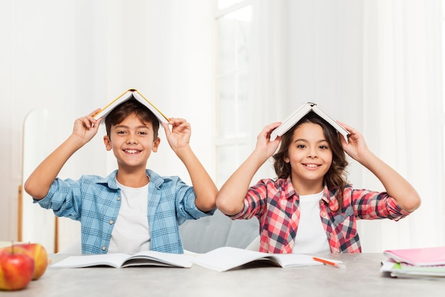 Siblings at home with books on top of head