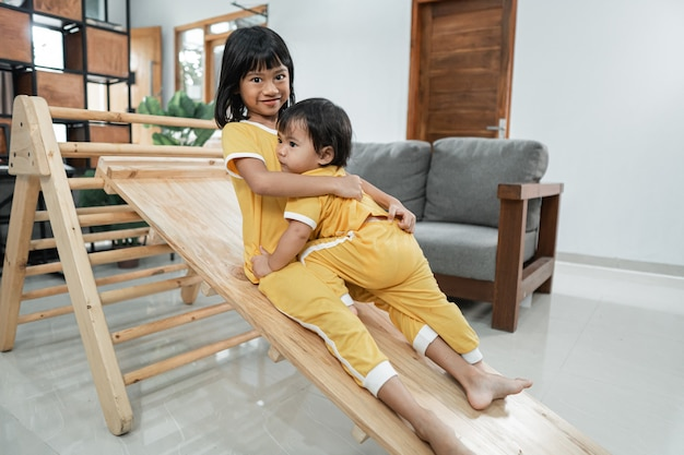 The siblings hug while playing slide in the pikler triangle toy together in the living room