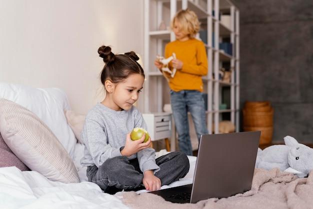 Братья и сестры в постели смотрят видео на ноутбуке