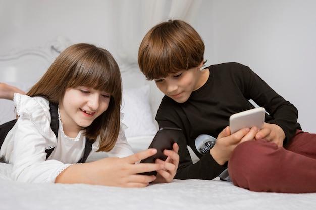 Братья и сестры в спальне с телефоном