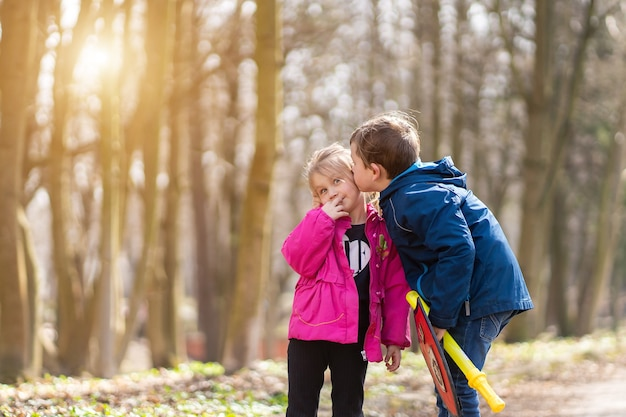 Братья и сестры дети играют с кленовыми листьями в осеннем парке