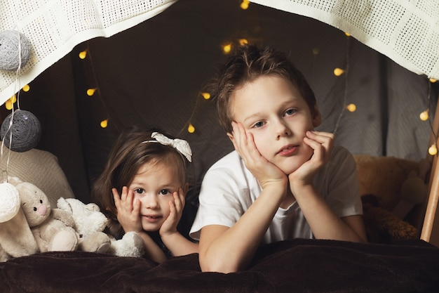 Братья и сестры лежат в хижине из стульев и одеял. брат и сестра улыбаются, играют дома