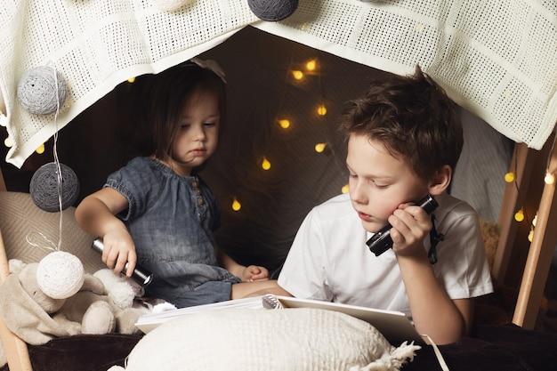 형제 자매는 의자와 담요의 오두막에 누워 있습니다. 형제와 자매, 집에서 손전등으로 책을 읽고