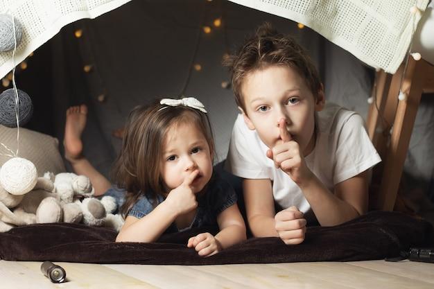 Братья и сестры лежат в хижине из стульев и одеял. брат и сестра показывают знак тишины, играя дома
