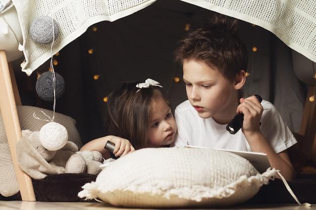 형제 자매는 의자와 담요 오두막에 누워 있습니다.