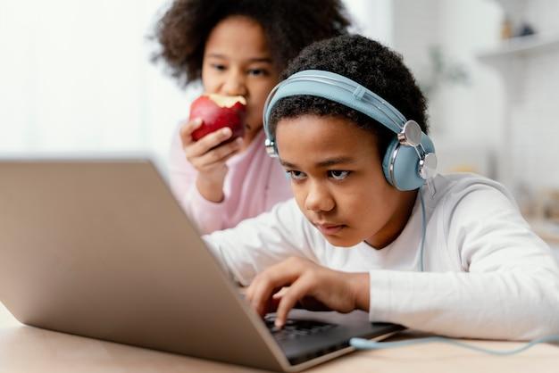 음악을 듣고 노트북을 사용하는 형제 자매