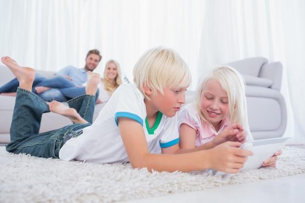 Siblings lying on the carpet using digital tablet