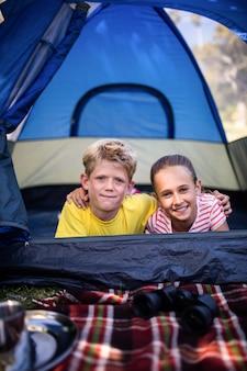 Siblings lying in a tent
