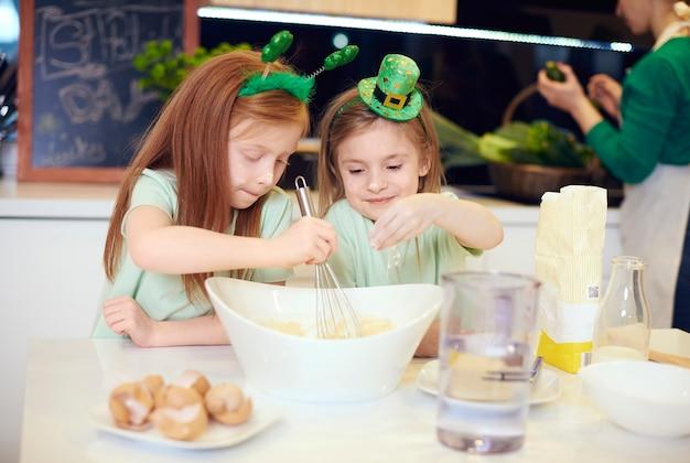 Братья и сестры, делающие печенье на кухне
