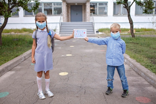 Siblings in medical mask hold picture with back to school message offline and social distance rules