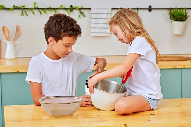 台所でペストリーの生地を混合する兄弟