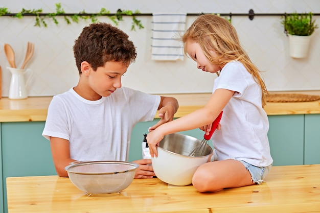 Siblings mixing dough for pastry in kitchen