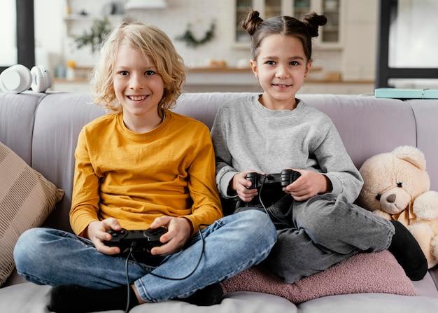 Братья и сестры на диване с джойстиками играют