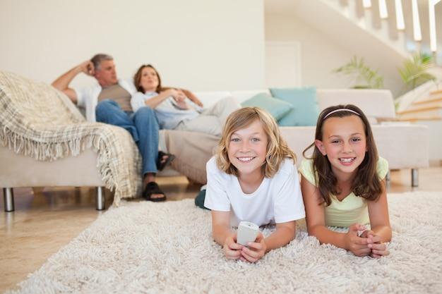 Братья и сестры на полу смотрят телевизор