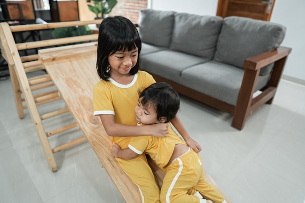 Siblings patiently keep playing the slide on the pikler triangle toy together in the living room