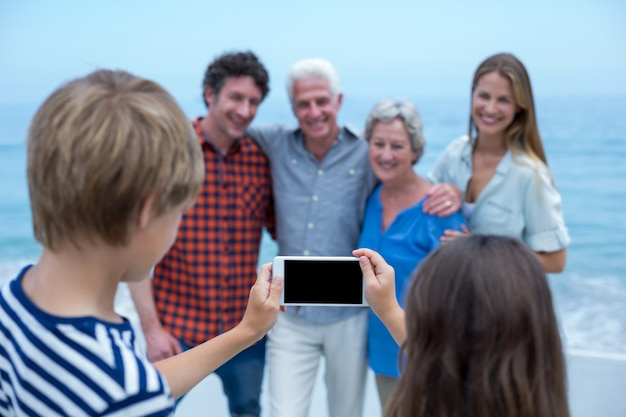 Siblings photographing family with smartphone