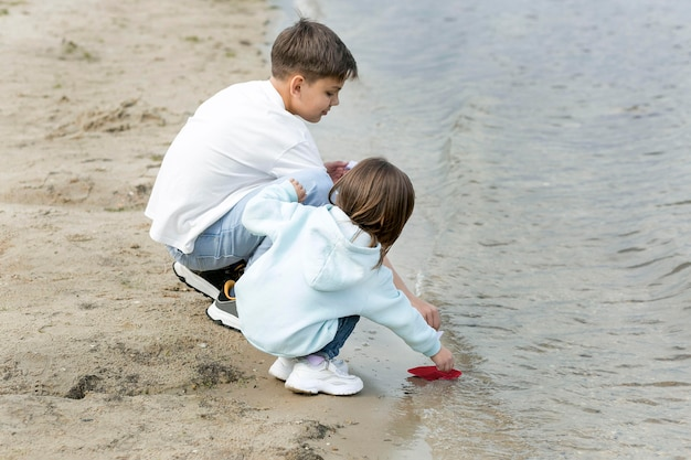 Siblings playing by the lake