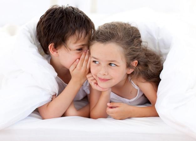親のベッドで遊んでいる兄弟