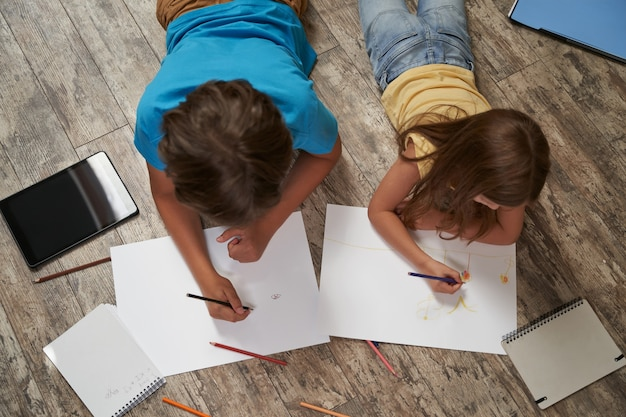 木の床に横たわっている小さな男の子と女の子の家の上面図で一緒に遊んでいる兄弟と