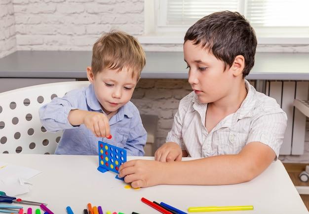 Братья и сестры вместе играют в настольную игру дома