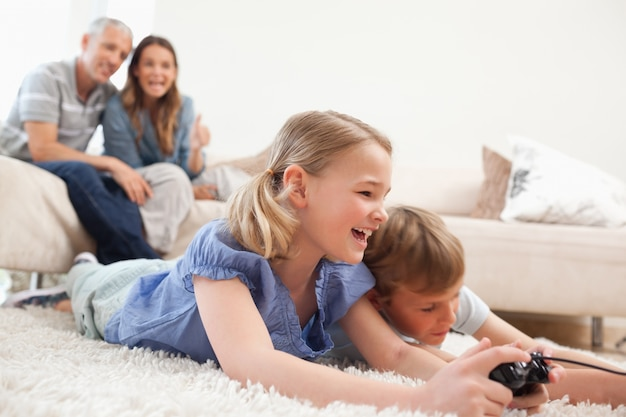 Siblings playing video games with their parents on the backgroun