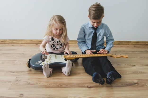 Siblings playing with a guitar