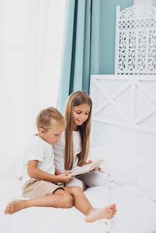 Siblings reading together a book