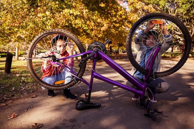 Братья и сестры ремонтируют велосипед