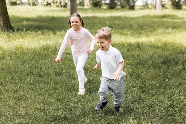 Братья и сестры бегут в парке
