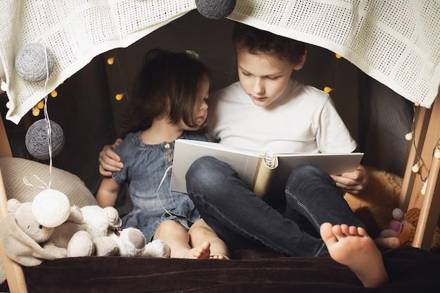 형제 자매들은 의자와 담요로 된 오두막에 앉아 있습니다. 형제와 자매, 집에서 손전등으로 책을 읽고