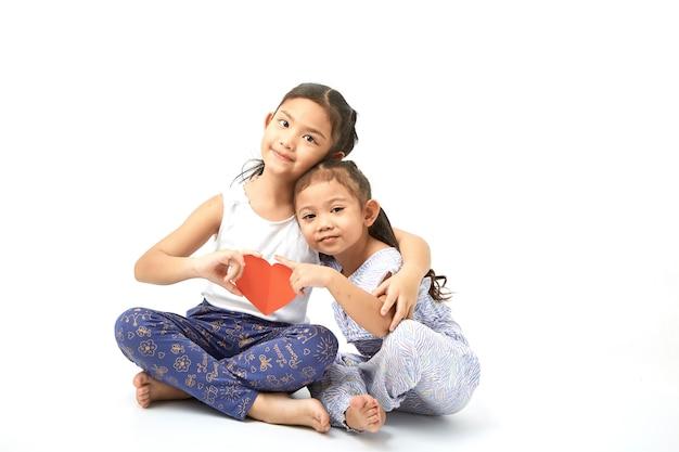 Siblings sitting of cute asian girl