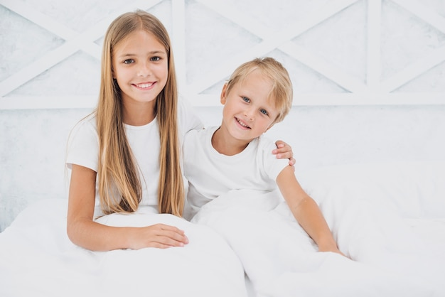 Siblings staying in bed while looking at the camera