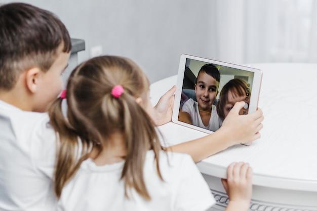 디지털 태블릿에서 자화상을 찍는 형제 자매