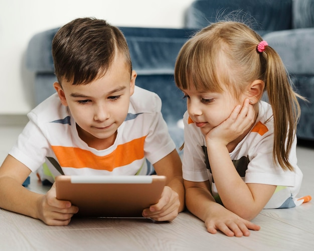 Siblings using a digital tablet front view