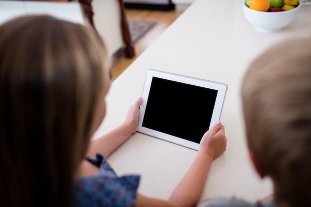 Siblings using digital tablet