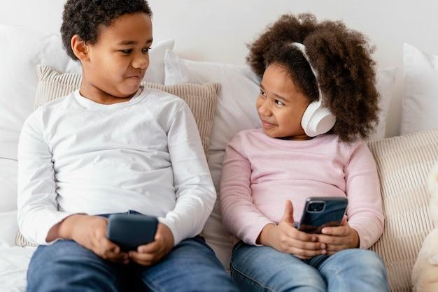 휴대폰을 사용하는 형제 자매