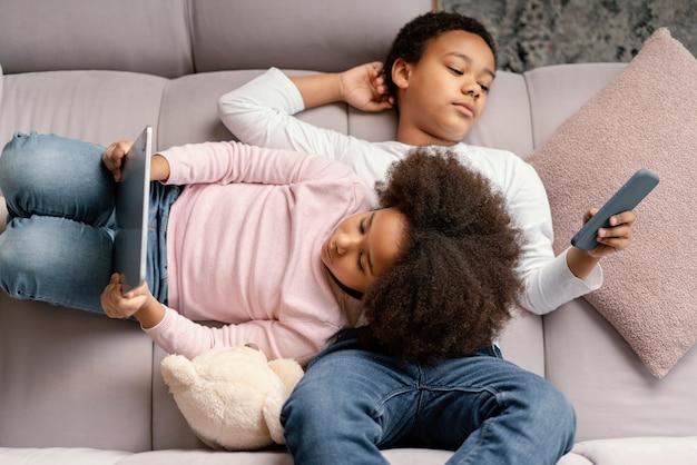 집에서 태블릿과 모바일을 사용하는 형제 자매